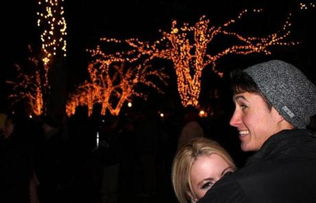 for G - 22youngholidays - Strolling Boston College students Colin Murphy and Katie Severance take in the lights along the Commonwealth Avenue mall. The entire walking corridor is lit up to create a winter spectacle for city residents during the holiday season. (Kade Krichko)