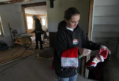 Stockbridge, VT - 12-18-11- Hallie Mendell (cq) looks over her Christmas stockings she found in the basement of her home was damaged during the floods of Tropical Storm Irene. Boyfriend Brett Forrest (cq) repairs the home in background. (Globe staff photo / Bill Greene) section:met, reporter:filipov, topic:25irene