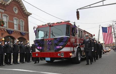 BOSTON, MA 12/ 30/ 2011: A salute by the Peabody firehouse as the Engine carries the casket for Peabody Firefighter funeral of James Michael Rice in Peabody at St John the Baptist Church. ( David L Ryan / Globe Staff Photo ) SECTION: METRO TOPIC : 31peabody REPORTER