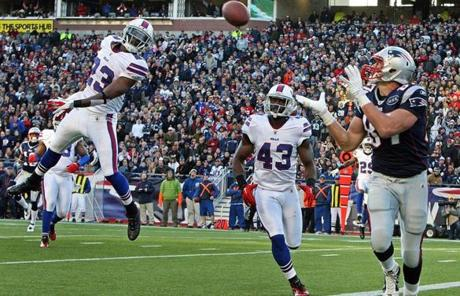 Defenders Aaron Williams (left) and Bryan Scott are powerless to stop Rob Gronkowski from giving the Patriots a 28-21 lead with a third-quarter TD reception.