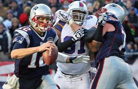By throwing for 338 yards and three touchdowns, Patriots QB Tom Brady  (above, getting some help from Matt Light) surpassed the 5,000-yard mark for the season.
