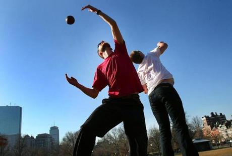 Boston, Mass -01/07/12 - GrahamTuttle(left) and his brother Ian from Boston go up for a pass while playing football in their t-shirts on Boston Common Globe staff photo by John Tlumacki (metro)