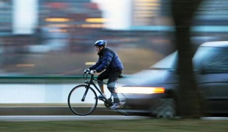 1-11-12: Cambridge, MA: A bicyclist is about to be passed by a car as they both navigate along Memorial Drive this afternoon. (Globe Staff Photo/Jim Davis) section:metro topic:feature