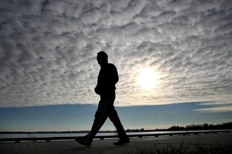 Boston,Mass. -01/11/12 - Dappled clouds obscure the late afternoon sun as a man walks along the sidewalk of Day Blvd. in South Boston. A major is expected to bring mostly rain to Boston on Thursday. Globe staff photo by John Tlumacki (metro)