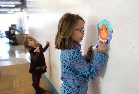 NO STORY -STAND ALONE PHOTO. BOSTON, MA -- Jan 11, 2012 -- Maya Hanley (cq) ,7, right, and her sister Fiona ,5, get a chance to draw on the wall as they spend their afternoon at dad's workplace. Their dad founder and CEO of netBlazr (cq) has office space at Mass Challenge where a giant brainstorming board fills the walls. (globe staff photo:Joanne Rathe section: FEATURE METRO )