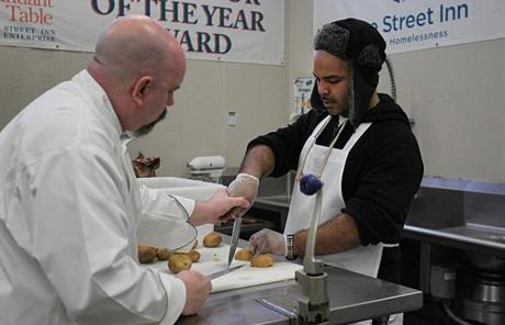 Boston, MA., 01/12/11, Trainees work in the Pine Street Inn kitchen with executive chef Frank Van Overbeeke, cq, the former chef of a French restaurant on Newbury Street. Pine Street runs a catering business out of the kitchen. He is on left. He helps trainee Raymond Matthews with cutting technique. Section; Business, Reporter; Katie Johnston Chase Suzanne Kreiter/Globe staff