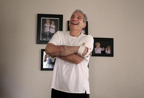 Revere, MA., 01/26/12, Richard Mangino, cq, lost his arms and legs ten years ago. Four months ago he got a double hand-transplant. We visit him at his home to see his progress. Photos of his grandchildren behind him. Section: Health Science, Reporter: Liz Kowalski Suzanne Kreiter/Globe staff