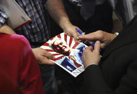 U.S. Republican presidential candidate and former Speaker of the House Newt Gingrich signs a photo of him after a Space Coast meeting in Cocoa, Florida January 25, 2012. Gingrich, cranking up the campaign rhetoric, mocked White House rival Mitt Romney's plan for self-deportation of illegal immigrants as a