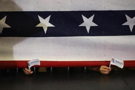 CAPE CANAVERAL, FL. 01/ 27/ 2012: Children hold Mitt Romney flags under a barrier where Mitt Romney spoke in Cape Canaveral at Astrotech Space Operations . ( David L Ryan / Globe Staff Photo ) SECTION: NATIONAL TOPIC : REPORTER