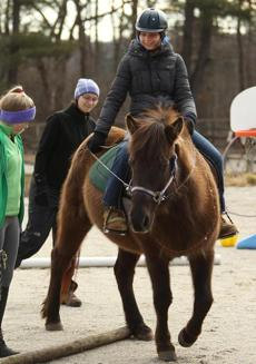 Hopkinton, MA 012812 Volunteer Kailyn Stephens (cq), 15, of Mendon (wearing green), and instructor Nicole Majkut (cq) right, walk alongside 20-year old Jona Ghelli (Cq),18, of Holliston at the At the Equine Parts Inc a.k.a. Therapeutic Equestrian Center in Hopkinton on Saturday January 28, 2012. (Essdras M Suarez/ Globe Staff)/ NOWK