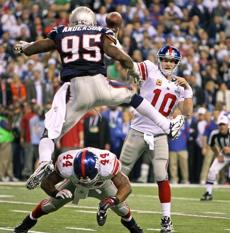 02-05-12: Indianapolis, IN: Patriots DB Mark Anderson (95) leaps high to try and avoid the low block of the Giants Ahmad Bradshaw, but Giants quarterback Eli Manning gets off a pass that was complete to Hakeem Nicks (not pictured) that set up the game winning touchdown. The New England Patriots meet the New York Giants in Super Bowl XLVI at Lucas Oil Stadium. Section: Sports topic:Super Bowl (Globe Staff Photo/Jim Davis)