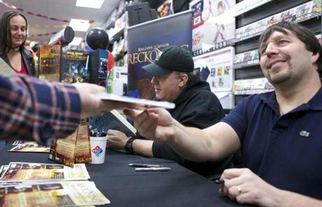 BELLINGHAM, MASSACHUSETTS -- 02/06/2012 -- Curt Schilling, center, and R.A. Salvatore, right, meet with fans at Game Stop during the release of Schillings newest video game Kingdoms of Amalur: Reckoning late on Monday evening in Bellingham. Brian Feulner for the Boston Globe