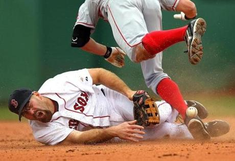Red Sox third baseman Kevin Youkillis grimmaces in the 5th inning as he covers 2nd base taking a throw from Jed Lowrie. The Angels' Peter Bourjos crashes into him. Youkillis lost control of the ball on the collision. (May 5, 2011)
