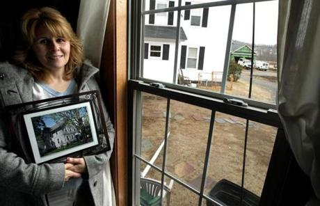 Kim Slozak and her family now live in a trailer. The house in which she grew up is visible through the  window.