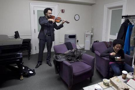 Juan Miguel Hernandez practiced in the green room before performing as Melissa White ate.