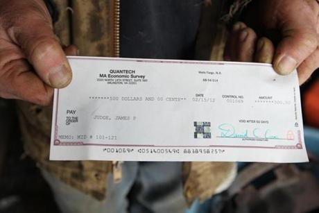 Pat Judge shows the $500 check he was given by the government to give up his right to fish for one year.
