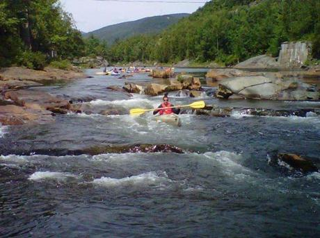 Kayakers paddle along the Pemigewasset River.