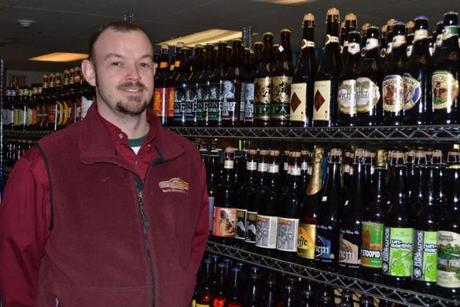 Owner Chris Clermont displays a few of the more than 700 varieties of beer at Waynes Market in North Woodstock, N.H.