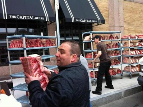 BACK BAY ,MA -- 03/13/12 --(large iPhone photo) 14m) Workers outside the Capital Grille form an assebly line to get meat onto truck as soon as possible after power outage has the Back Bay without power through Wedneday. (globe staff photo:Joanne Rathe section: metro reporter: topic: 15Copleyfire )