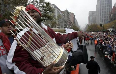 David Ortiz showed off the World Series trophy to fans along the route.