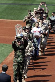War veterans carried the World Series trophy and the team's championship rings onto the field.
