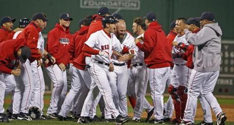The Red Sox converged on Youkilis to celebrate his run that sent the series back to Florida.