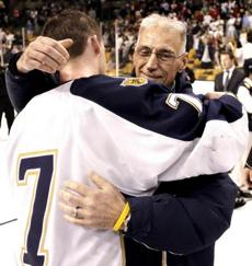 Malden Catholic's Brendan Collier hugs former coach Chris Serino after the state title game.