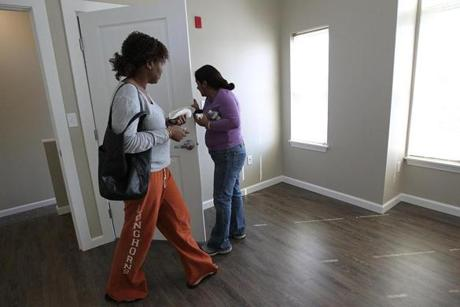 South Boston, MA., 03/20/12, The Homes at Old Colony had a ribbon cutting and grand opening ceremony today. Checking out a model unit is Aissata Camara, left, and Aracelly Tyrell, cq. They are residents of the older building in the project. Section: Metro, Reporter: Billy Baker Globe staff/Suzanne Kreiter