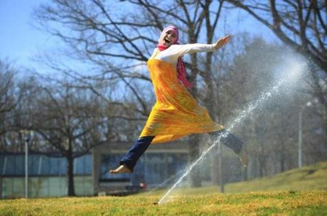 Rawda Aljawhary, a junior at Brandeis University, leaped through sprinklers that showered students with relief during the summer-like day. March 22, 2012.