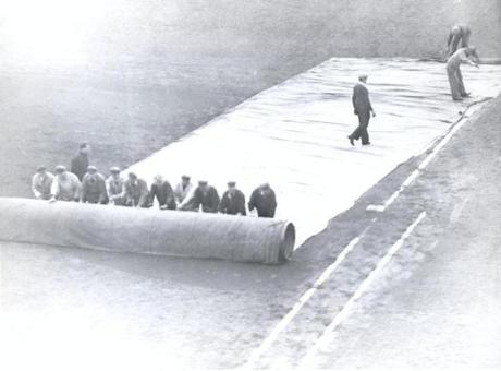 The grounds crew rolled out the tarp during a rainstorm in 1937.