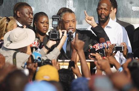 The Rev. Al Sharpton spoke at a rally with Tracy Martin (right) and Sybrina Fulton (2d left), the parents of Trayvon Martin.