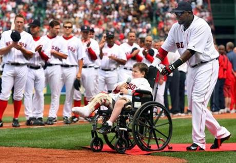 David Ortiz helped Jimmy Fund patient Jordan Leandre, 5, to the plate, where he sang the national anthem on Opening Day in 2006.