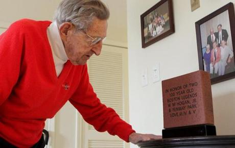 "Bill Hogan looks at a commemorative brick celebrating ""two 100-year-old Boston legends'' given to him by his family."