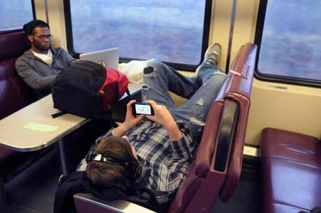 Brian Moyer of Franklin got comfortable on the nearly empty Plymouth/Kingston train while using his mobile device.