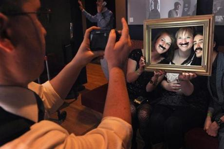 Sam Cousins of Portland, Maine, took a photo portrait of Alana Iannucci of Wilmington, Del., and Kelsey Cler and Alexander Jones of Winslow, Maine, who sported fake mustaches.
