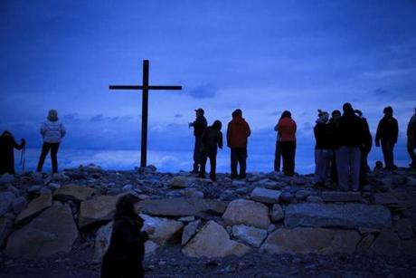 Several hundred people gathered at the Scituate Harbor lighthouse at dawn for an Easter morning service led by Pastor Dan Eddy of Christ Lutheran Church in Scituate. April 8, 2012.