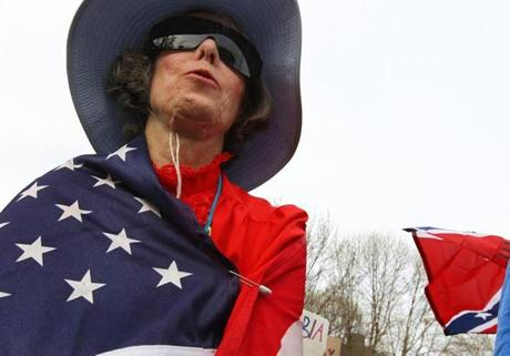 Christina Gordon of Watertown wrapped herself in a flag while attending the Mass Tea Party's Patriots Day Rally in Boston.