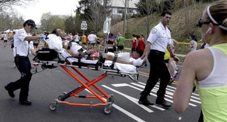 A runner was transported across Commonwealth Avenue from the medical tent to an ambulance at Heartbreak Hill in Newton Monday.