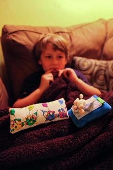Adam Jerrett, 7, fiddled with his loose tooth near the pillows where he keeps his teeth for the Tooth Fairy.