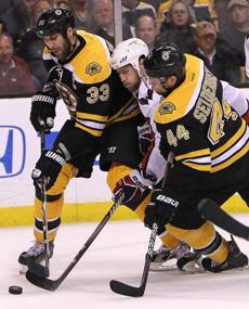 Zdeno Chara and Dennis Seidenberg  put the squeeze on Washington Capitals center Brooks Laich during the third period.