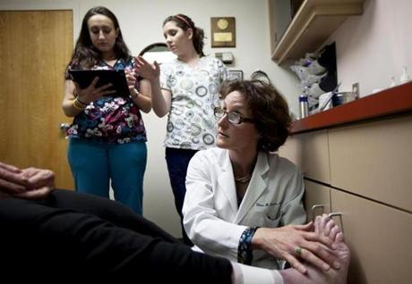 Concord dermatologist Eileen Deignan checked on a patient while medical assistants Stina McKenna, left, and Jen Pratt took notes on iPads on May 7.