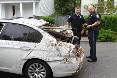 Police surveyed the damage to the car after it was removed from the house by a tow truck.
