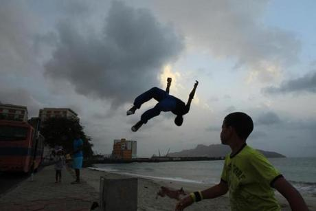 Young men practice parkour moves off a beachfront wall in Cape Verde.