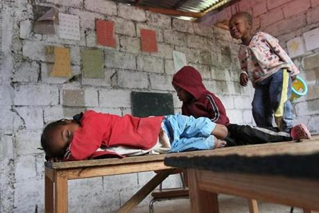 Stephanie, 8, falls asleep on a desk as other children play.