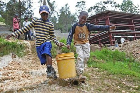 Schneider, 12, and Jeanele, 10, carried buckets of rocks after school to build an area for garbage for the new house.