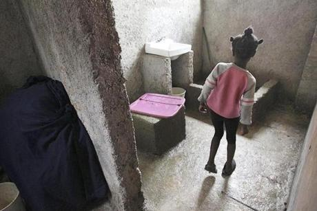 There is one toilet for all 60 children. It is a hole covered by cement which leads to the open hillside behind the house. There is no running water for the sink Kelette, 8, would have to use.