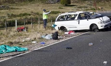 Police examined the scene of the minivan crash that killed three Boston University students in NewZealand. Some of the students, probably without seat belts, were thrown out of the van. All the students in the wrecked van were killed or injured.