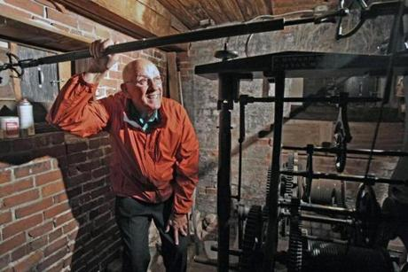 Former Walpole building superintendent Jim Clerici inpects the clock mechanism inside the tower at Old Town Hall. A consultant to the town is recommending the historic building, which currently serves as the police station, be converted into office space for the Fire Department.