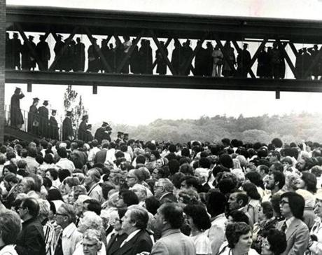 June 2, 1977: Members of the 1977 graduating class moved across the covered walkway above the crowd gathering on the UMass-Boston campus for commencement exercises. Speakers at the graduation attended by some 3,500 guests included UMass-Boston Chancellor Carlo L. Golino and student orators William J. Powers of Saugus and Thomas McShane of Brighton.