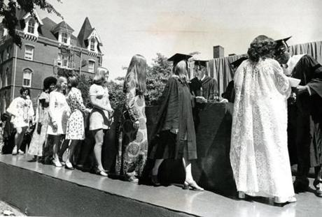 June 3, 1973: Tufts women, with one exception, wore various syles of dresses as they receive their diplomas. Tufts, along with other universities, chose to forego the traditional garb and contribute the rental fees to useful social and anti-war purposes. The commencement address that year was given by US Rep. Barbara Jordan from Texas who spoke on the continued bombing of Cambodia in the face of congessionial votes in opposition and the continued impoundment of funds by President Richard Nixon.